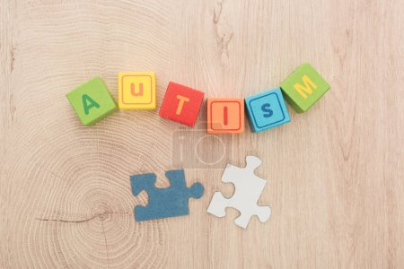 Photo for Top view of autism lettering made of multicolored cubes near puzzle pieces on wooden table - Royalty Free Image