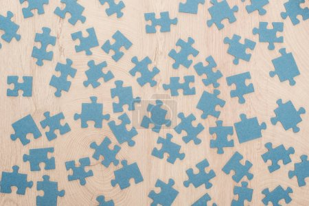 Photo for Top view of blue puzzle parts scattered on wooden table - Royalty Free Image