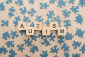 top view of autism lettering made of wooden blocks among puzzle pieces on wooden table