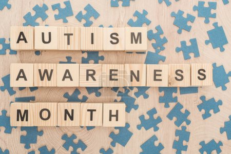 Photo for Top view of autism awareness month lettering made of wooden blocks among puzzle pieces on wooden table - Royalty Free Image