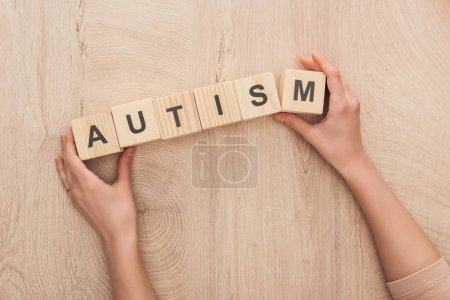 Photo for Cropped view of woman holding wooden cubes with autism lettering - Royalty Free Image