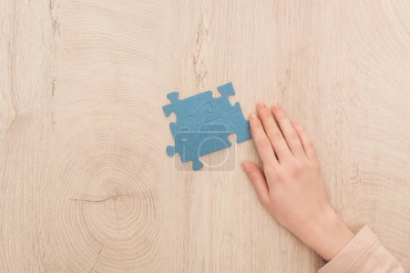 Photo for Cropped view of female hand near blue puzzles on wooden table - Royalty Free Image