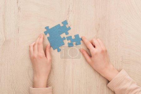частичный вид женских рук с голубыми головоломками на деревянном столе