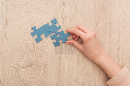 Photo for Partial view of female hand with blue puzzles on wooden table - Royalty Free Image