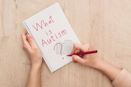Photo for Partial view of woman writing in notebook what is autism question on wooden table - Royalty Free Image