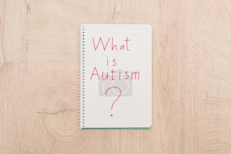 Photo for Top view of red what is autism question written in notebook on wooden table - Royalty Free Image