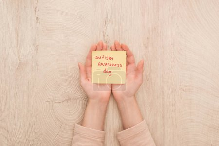 Photo for Cropped view of female hands and sticky note with red autism awareness day handwritten lettering - Royalty Free Image