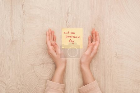 Photo for Partial view of female hands and sticky note with red autism awareness day handwritten lettering - Royalty Free Image