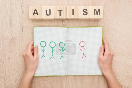 Photo for Cropped view of woman holding opened notebook with drawn different humans near wooden cubes with autism lettering - Royalty Free Image