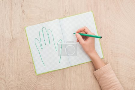 Photo for Cropped view of female hand on opened notebook near drawn human palm - Royalty Free Image