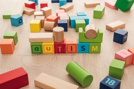 Photo for Autism lettering made of multicolored cubes among building blocks on wooden surface - Royalty Free Image
