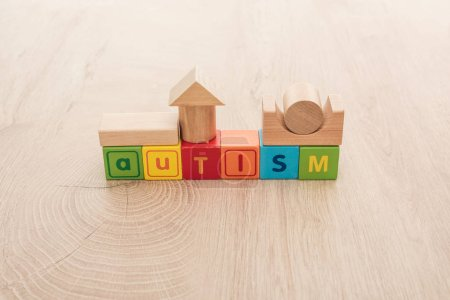Photo for Autism lettering made of colorful cubes with building blocks on wooden surface - Royalty Free Image