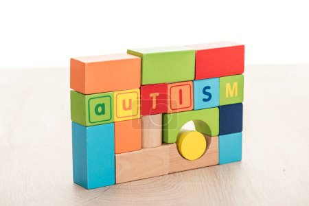 Photo for Autism lettering made of multicolored building blocks on wooden surface isolated on white - Royalty Free Image