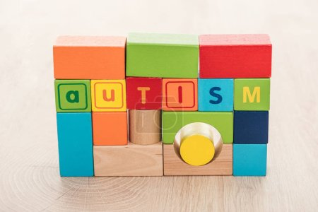 Photo for Autism lettering made of colorful building blocks on wooden surface - Royalty Free Image