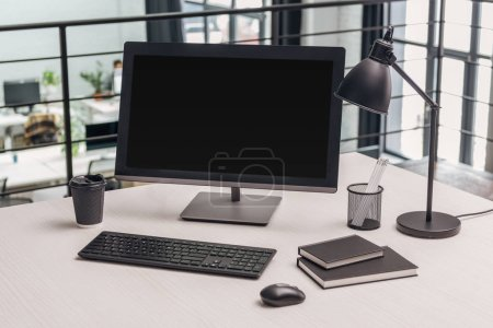 Photo for Modern workplace with computer, coffee to go, lamp and stationery in office - Royalty Free Image