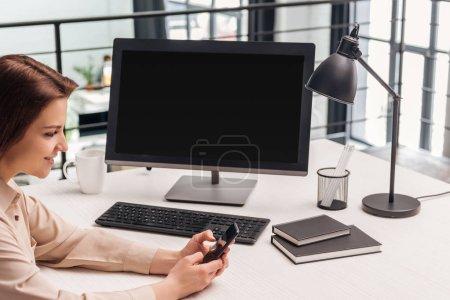Photo pour Mise au point sélective de femme souriante à l'aide de smartphone près d'ordinateur au lieu de travail au bureau - image libre de droit