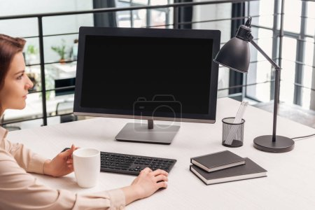 selective focus of woman sitting with cup near computer at workplace in office