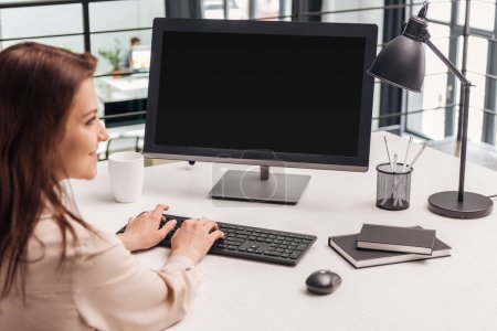 Photo for Selective focus of smiling woman using computer at workplace - Royalty Free Image