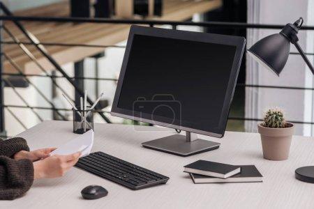 Photo pour Vue recadrée de femme tenant des papiers sur lieu de travail dans le bureau moderne - image libre de droit