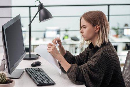 Foto de Muchacha triste de rasgado de papel en el lugar de trabajo en la oficina moderna - Imagen libre de derechos