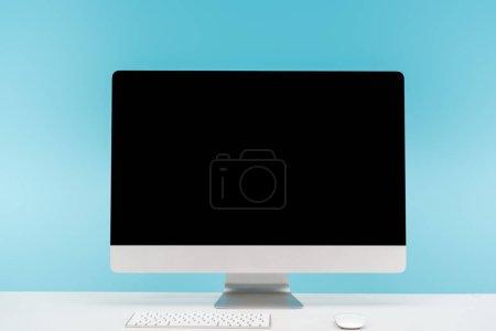 Photo pour Lieu de travail avec la souris d'ordinateur moniteur, clavier et l'ordinateur sur une table blanche sur fond bleu - image libre de droit