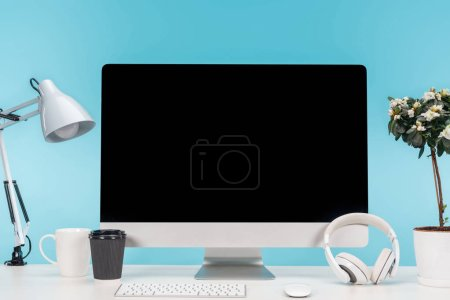 Photo for Workplace with computer, lamp, cup, coffee to go, headphones and flowerpot on white table on blue background - Royalty Free Image