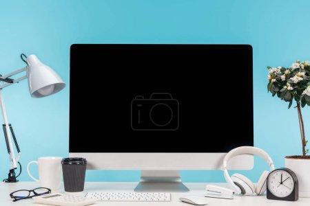 Foto de Lugar de trabajo con computadora, lámpara, taza, café para llevar, calculadora y auriculares en mesa blanca sobre fondo azul - Imagen libre de derechos