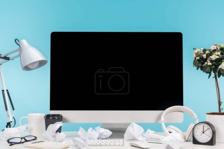 Photo for Messy workplace with computer, lamp, cup, coffee to go, crumpled papers, headphones and flowerpot on white table on blue background - Royalty Free Image