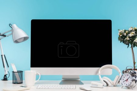 Photo for Workplace with computer, lamp, stationery and headphones on white table on blue background - Royalty Free Image
