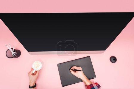 Foto de Vista parcial del hombre usando tableta gráfica y celebración taza con café sobre fondo rosa - Imagen libre de derechos