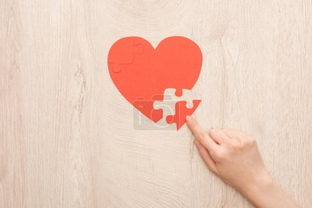 Photo for Cropped view of woman pointing with finger to puzzle of heart - Royalty Free Image