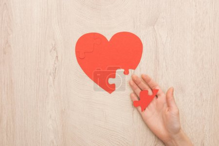 Photo for Cropped view of woman holding puzzle of heart on wooden background - Royalty Free Image