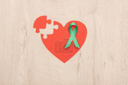 Photo for Top view of bright paper heart and green ribbon on wooden background - Royalty Free Image