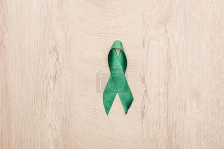 top view of green ribbon on wooden background with copy space