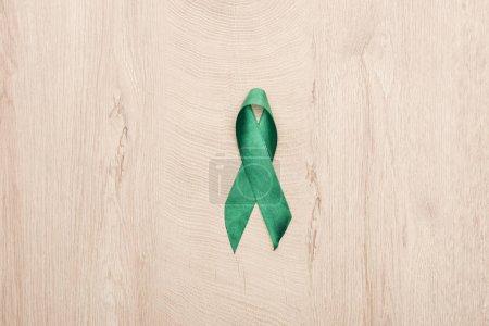 Photo pour Vue du dessus du ruban vert sur fond en bois avec espace de copie - image libre de droit