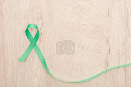 Photo for Top view of green and colorful ribbon on wooden background with copy space - Royalty Free Image