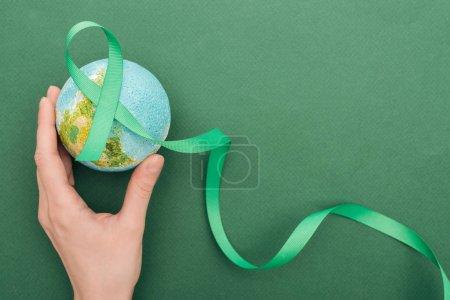 Photo pour Vue recadrée de la femme retenant la terre de jouet et le ruban sur le fond vert - image libre de droit