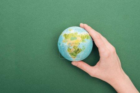 Photo pour Vue partielle de la femme retenant la terre de jouet sur le fond vert avec l'espace de copie - image libre de droit
