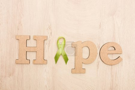 Photo for Top view of wooden word hope and green ribbon on wooden background - Royalty Free Image