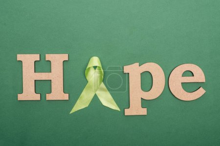 Photo for Top view of wooden word hope and green ribbon on colorful background - Royalty Free Image