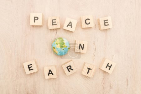 top view of cubes with peace on earth lettering and toy planet on wooden background