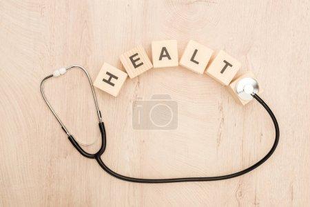 Photo pour Vue de dessus des cubes avec le lettrage de santé et le stéthoscope sur le fond en bois - image libre de droit