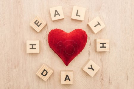 top view of cubes with health day lettering and toy heart on wooden background