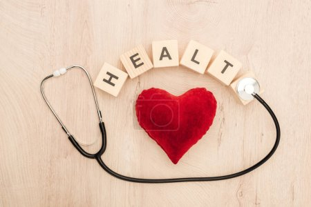 top view of cubes with health lettering, toy heart and stethoscope on wooden background