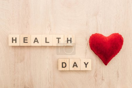 Photo for Top view of cubes with health day lettering and toy heart on wooden background - Royalty Free Image