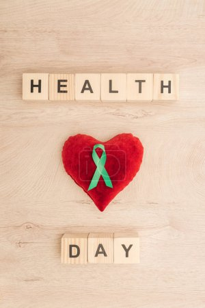 Photo for Top view of cubes with health day lettering, toy heart and green ribbon on wooden background - Royalty Free Image