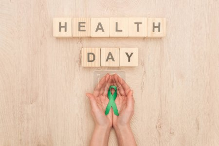 top view of woman holding green ribbon and cubes with health day lettering