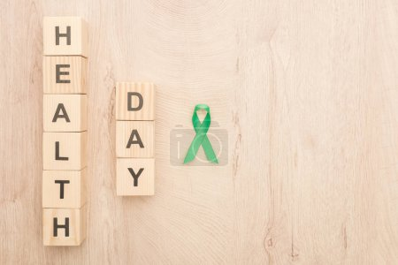 Photo for Top view of cubes with health day lettering and green ribbon on wooden background - Royalty Free Image