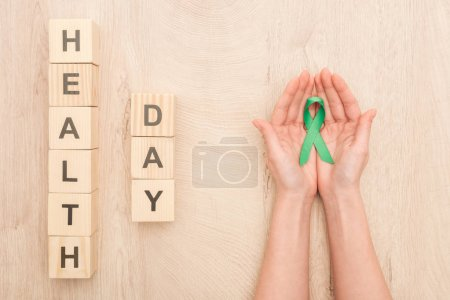 Photo for Partial view of woman holding green ribbon and cubes with health day lettering - Royalty Free Image