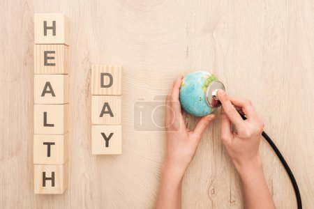 Photo for Partial view of woman holding stethoscope, toy heart and cubes with health day lettering - Royalty Free Image